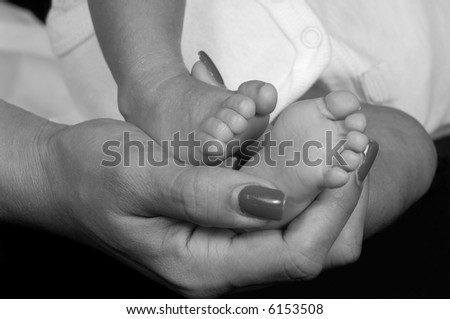 Mother's Hand Holding Baby's Feet