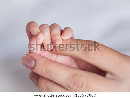Mother's hand holding small hand  her baby