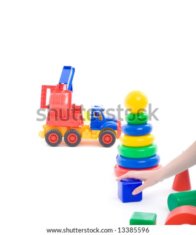 Mother's hand put cube on floor and invite baby to play with toys on playground. Image isolated on white with light shadows