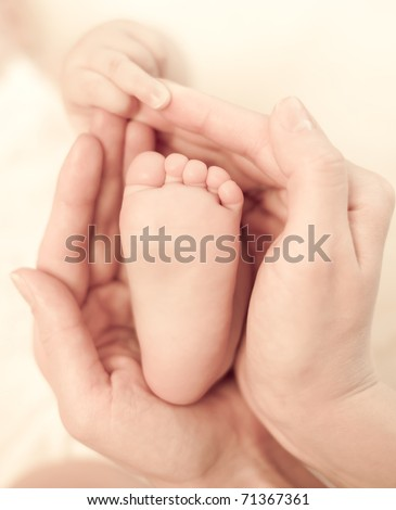 Mother's hands carefully keeping baby's foot with tenderness - stock photo