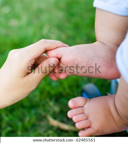 Mother's hands cradling her infant son's feet, close-up - stock photo