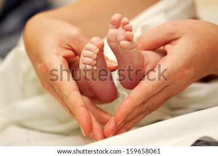 Mother's hands forming a heart frame for the tiny feet of her newborn baby. - stock photo