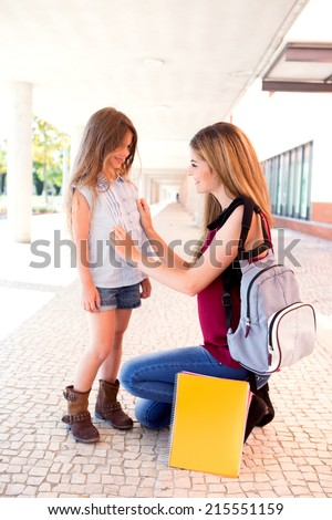Mother saying goodbye to her daughter at school - stock photo