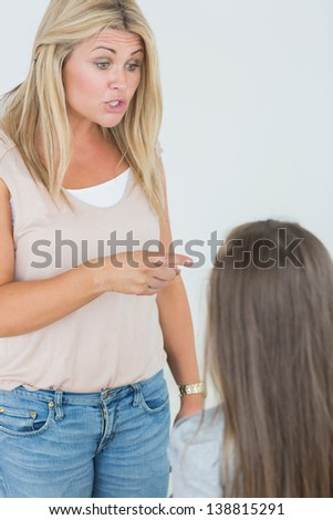 Mother scolding her daugher and pointing - stock photo