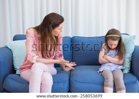 Mother scolding her naughty daughter at home in the living room - stock photo