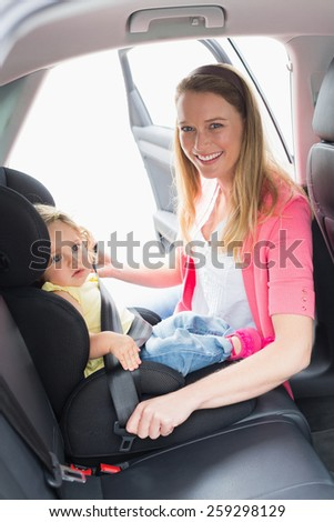 Mother securing her baby in the car seat in her car - stock photo
