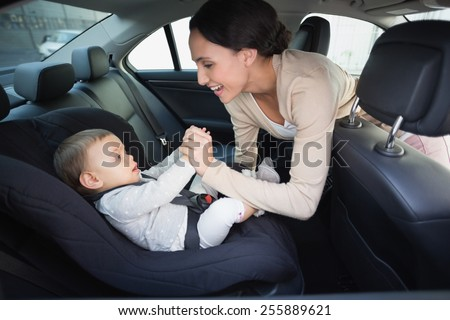 Mother securing her baby in the car seat in the car - stock photo