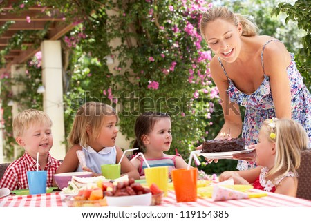 Mother Serving Birthday Cake To Group Of Children Outdoors - stock photo