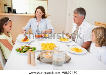 Mother serving dinner to her family - stock photo