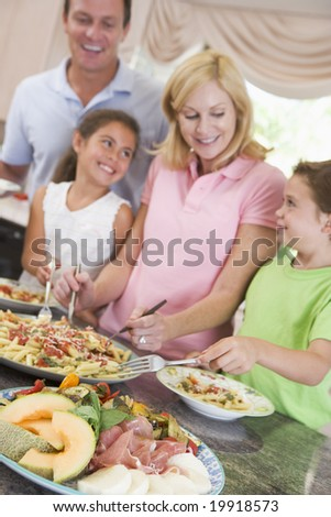 Mother Serving Up Dinner For Family - stock photo