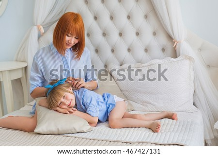 Mother sets hair to her little daughter in the morning