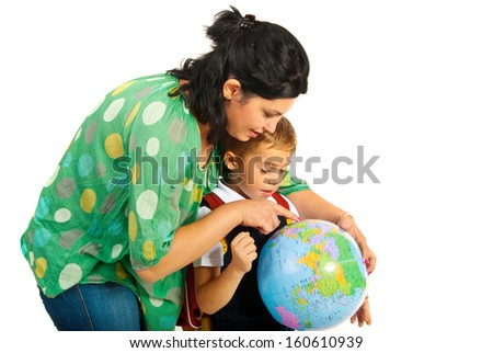 Mother showing countries to her son on a world globe - stock photo