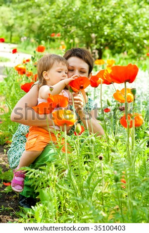 Mother showing flowers to her little daughter - stock photo