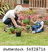 Mother showing her daughter a purple flower in their garden - stock photo