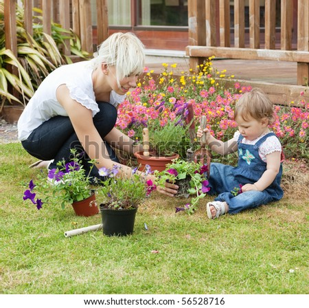 Mother showing her daughter a purple flower in their garden