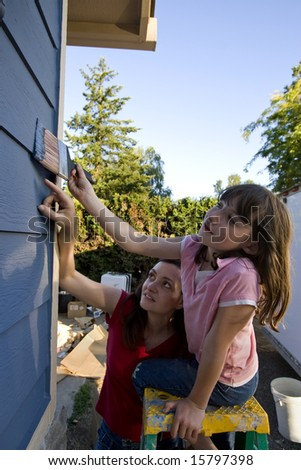 Mother showing her daughter where to apply paint as they paint their house. Vertically framed photograph. - stock photo