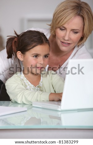 mother showing her little girl how to use the laptop - stock photo