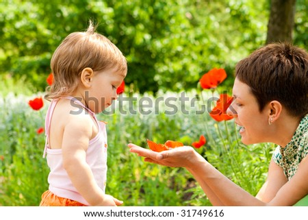 Mother showing poppy flower to her daughter - stock photo