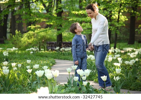 Mother shows to son blossoming white tulips in  garden - stock photo