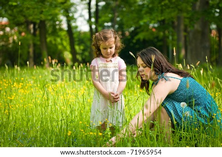Mother shows with finger to her cute little daughter something interesting in grass - stock photo