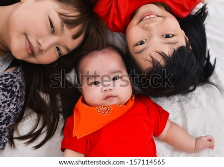 mother, sister and baby on the floor laying on - stock photo