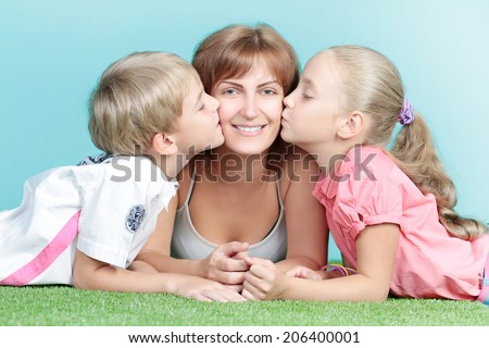 Mother sister and brother lying on the grass and children kissing woman - stock photo