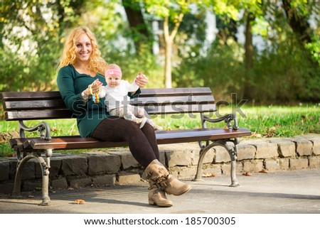 Mother sitting on a park bench with baby - stock photo