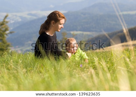 Mother sitting with child on meadow at mountains background - stock photo