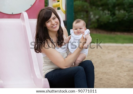 Mother sitting with her adorable daughter in playground - stock photo