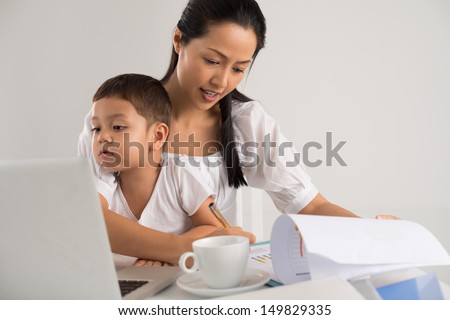 Mother sitting with her child and working at the same time - stock photo