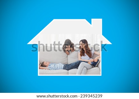 Mother sitting with her children on sofa against blue background with vignette - stock photo