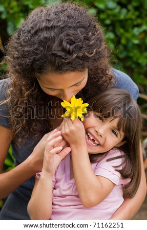 Mother smelling a flower with her daughter - stock photo