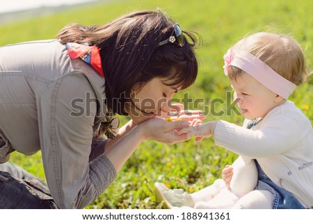 mother smelling dandelion in her palms - stock photo