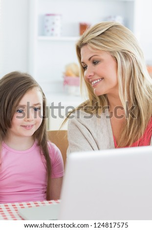 Mother smiling at Daughter using laptop in the kitchen