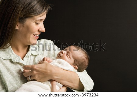 Mother smiling holding sleeping baby against black background. - stock photo