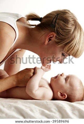 Mother smiling to her baby - stock photo