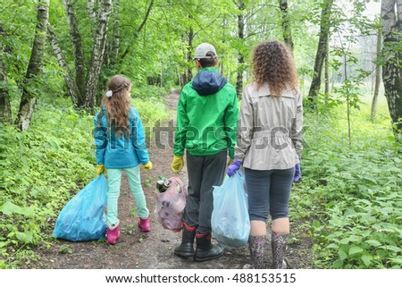 Mother son and daughter clean up in urban woodland, holding bags of garbage, seen from behind