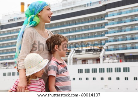 mother, son and daughter in dock, looking right, big cruise ship on background - stock photo