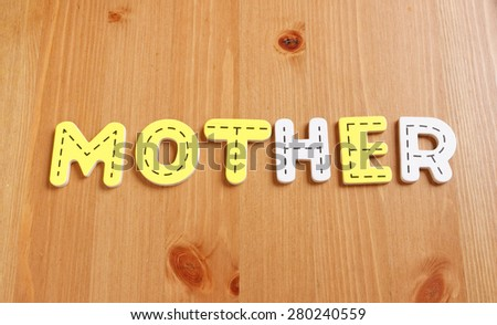 MOTHER, spell by woody puzzle letters with woody background - stock photo