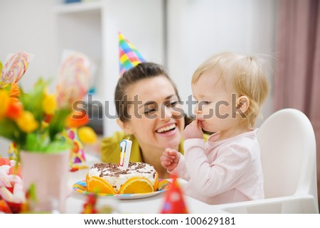Mother spending fun time with baby on birthday party - stock photo