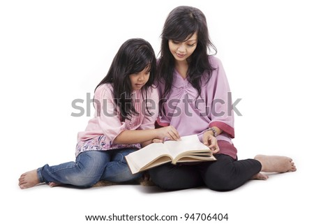 Mother spending the time together with her daughter reading a book - stock photo
