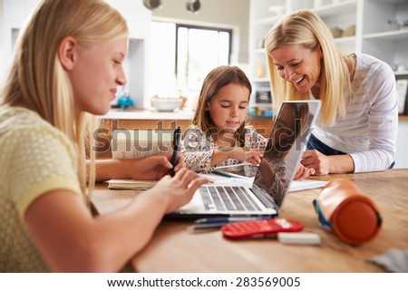 Mother spending time with daughters at home - stock photo