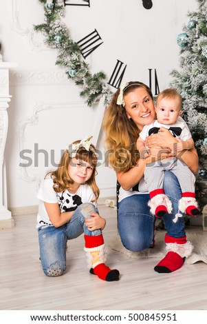 Mother spending time with son and daughter near Christmas tree