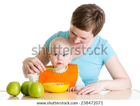 Mother spoon feeding her baby boy isolated