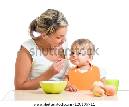 mother spoon-feeding her baby girl
