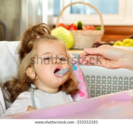 Mother spoon-feeds the child.  Feeding baby. Baby food. - stock photo