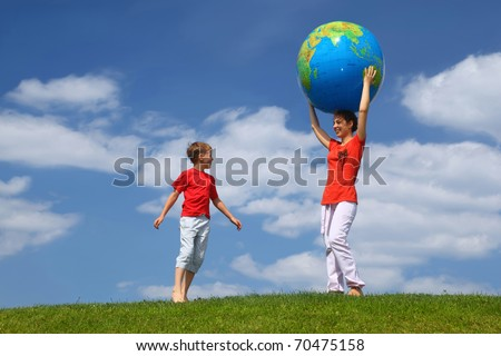 Mother stands on  grass and holds hands  large inflatable ball on  head,  boy comes running to it