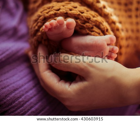 mother stroked the little feet of her child - stock photo