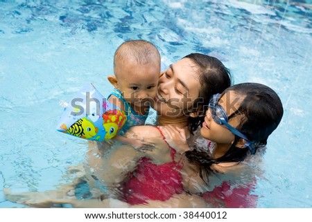 Mother swimming together with her kid - stock photo