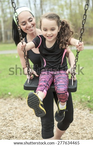 Mother swinging her daughter - stock photo